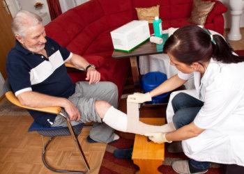 nurse applying bandage to patient's foot