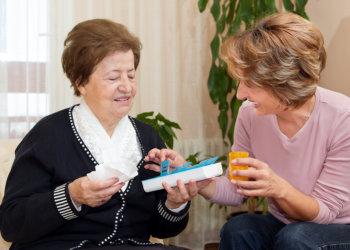 caregiver giving medicine to her patient
