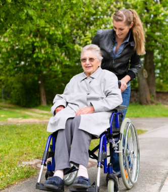 caregiver and elderly in wheelchair smiling