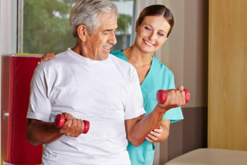 caregiver assisting man in exercising